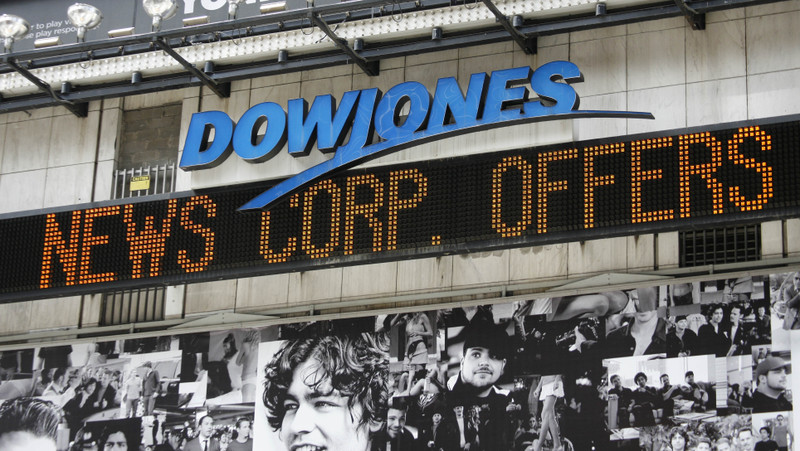 "Part of a news headline announcing that News Corp. has offered to buy Dow Jones for $60 a share is displayed on an electronic ""zipper"" under the Dow Jones logo in Times Square in New York on Tuesday, May 1, 2007. (AP Photo/Peter Morgan)"